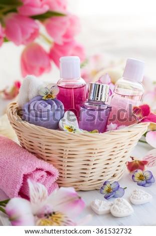 Spa bath toiletries set in basket with fresh flowers - stock photo