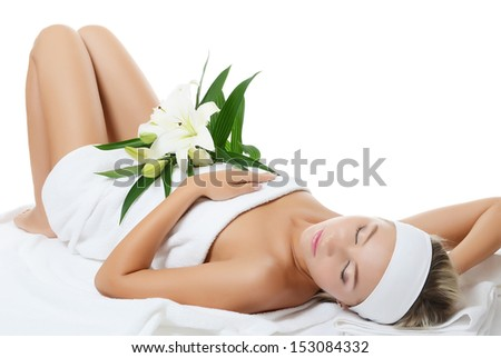 Spa beautiful woman lays with white lily - stock photo