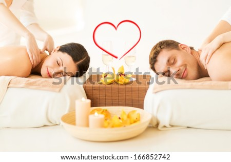 spa, beauty, love and happiness concept - smiling couple with candles, flowers and champagne glasses getting massage in spa salon - stock photo