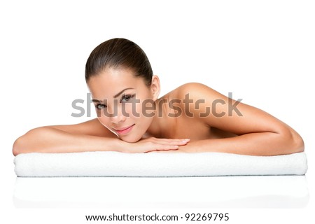 Spa beauty skin treatment woman on white towel. Gorgeous beautiful multiracial Caucasian / Asian female model with perfect skin lying on towel. Young woman in 20s isolated on white background. - stock photo