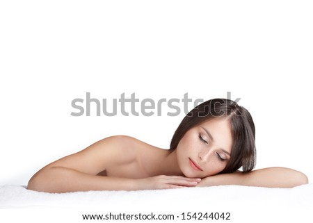 Spa beauty skin treatment woman on white towel. Woman with perfect skin lying on towel. Young woman in 20s isolated on white background. - stock photo
