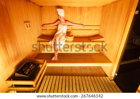 Spa beauty well being and relax concept. Woman in full length white towel sitting relaxed in wooden sauna - stock photo