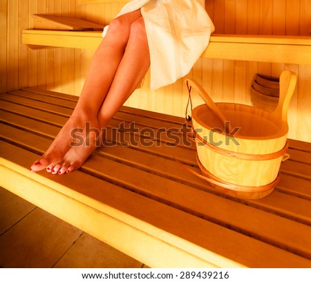 Spa beauty well being and relax concept. Woman white towel sitting relaxed in wooden sauna, part of body legs - stock photo