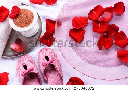 Spa bowl with water, rose petals, towel and slippers on light background. Concept of pedicure or natural spa treatment - stock photo