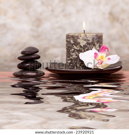 Spa candle and balanced stones with orchid - stock photo