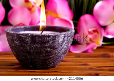 Spa candle and orchid on bamboo mat - stock photo