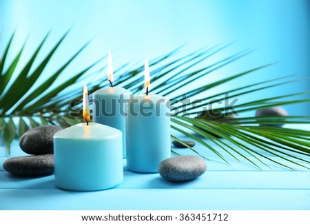Spa composition of blue candles, stones on blue background - stock photo