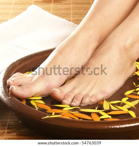 Spa composition of legs, ceramic bowl, towel and petals - stock photo