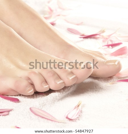 Spa composition of legs, towel and petals - stock photo