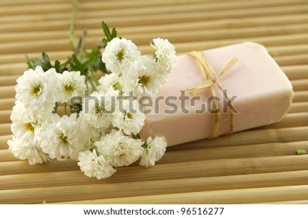 Spa composition. Soap and chrysanthemums on bamboo stick straw mat