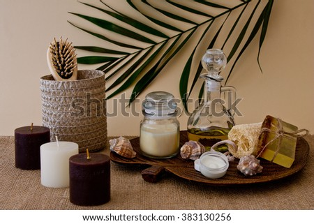 Spa composition with candles. Massage oil and cream, comb, soap, sponges and various hygiene products - stock photo