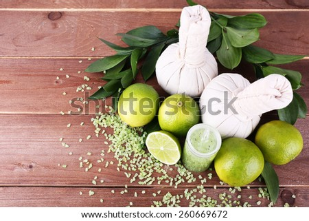 Spa composition with lime and compress balls on wooden table background - stock photo