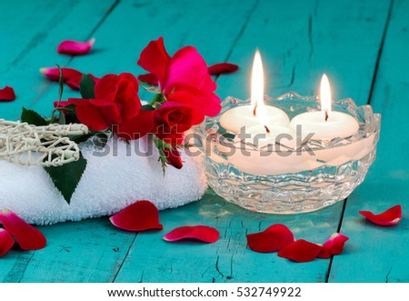 Spa composition with red flowers and rose petals, white towel, diffuser, aroma bowl with three white floating candles on antique rustic teal blue wood background; holiday background with copy space