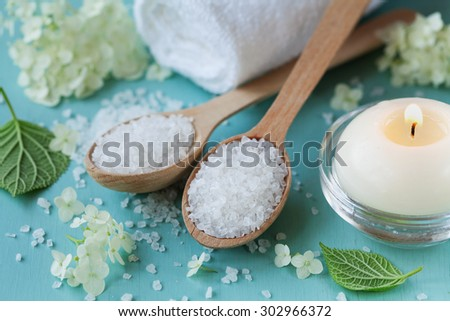 Spa composition with sea salt in wooden spoon, bath towel, white flowers and burning candles on a blue wooden surface, aromatherapy and skincare concept - stock photo