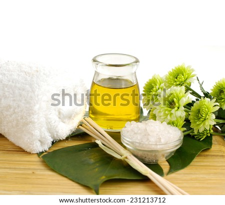 spa concept- bath salt in bowl with green flower and essential oil on board - stock photo