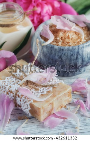 SPA concept: composition of spa treatment with natural sea salt, aromatic oil and peonies flowers on white wooden background