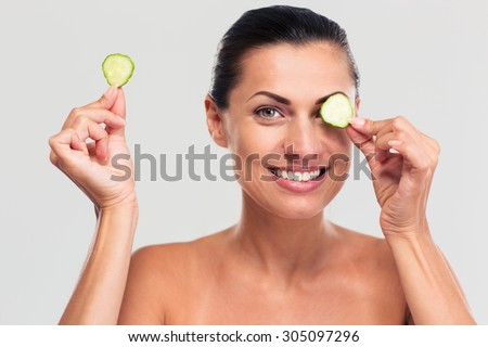 Spa concept. Happy woman covering her eye with cucumber and looking at camera isolated on a white background - stock photo