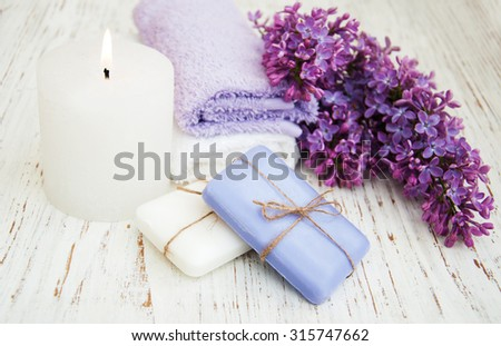 Spa concept - natural soap, towels and lilac flowers - stock photo