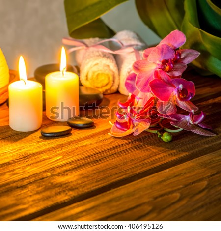 spa concept of pink orchid flower, thai herbal compress balls in basket, towels, zen stones and candles on wooden background, close up - stock photo