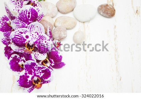 Spa concept of stones with drops, blooming twig stripped violet orchid on a wooden backgrounds - stock photo
