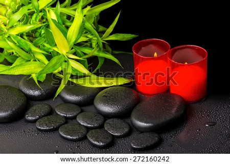 spa concept of twigs bamboo with dew and red candles on zen basalt stones - stock photo