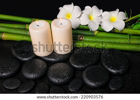 spa concept of zen basalt stones, three white flower frangipani, candles and natural bamboo with dew - stock photo