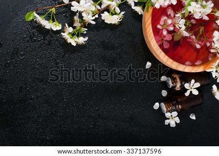 Spa concept on a dark background. Sea salt, flowering branches of cherry, aromatic oils - stock photo