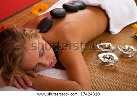 spa concept with a beautiful woman having volcanic stone massage - stock photo