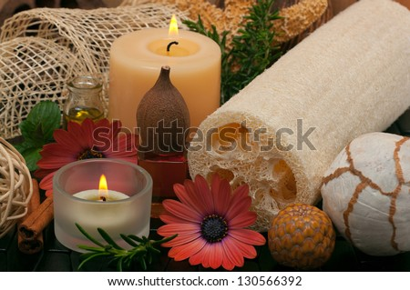 Spa concept with aromatic candles, herbs, beautiful daisies, massage oil and loofah - stock photo