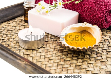 Spa concept with aromatic essence,soap and turmeric powder on tray decorated by cutter flower and lit tea candle decorated by cutter flower and lit tea candle - stock photo