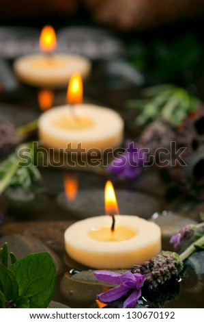 Spa concept with aromatic floating candles, herbs and lavender