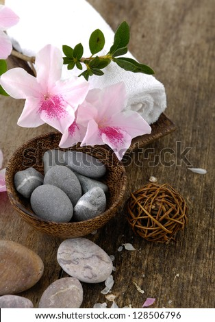 Spa concept with flower and zen stones in bowl on old wooden - stock photo