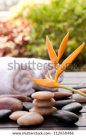 Spa concept with orange heliconia and zen stones outdoor - stock photo