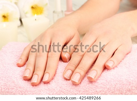 Spa concept. Woman hands with beautiful manicure and flowers on towel, close up