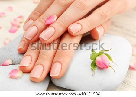 Spa concept. Woman hands with beautiful rose petals on wooden background, close up - stock photo