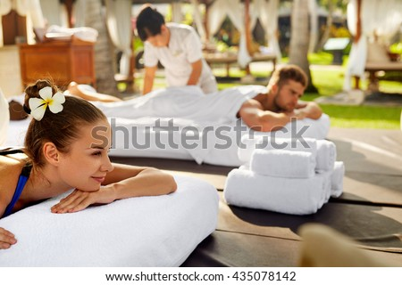 Spa Couple Massage. Beautiful Happy Smiling Woman And Healthy Man Enjoying Relaxing Body Massage Treatment Outdoors At Beauty Salon. People At Romantic Day Spa Resort. Health Care And Relax Concept - stock photo