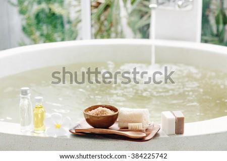 Spa decoration, natural organic products on a bathtube. Loofah, towel and frangipani flower - stock photo