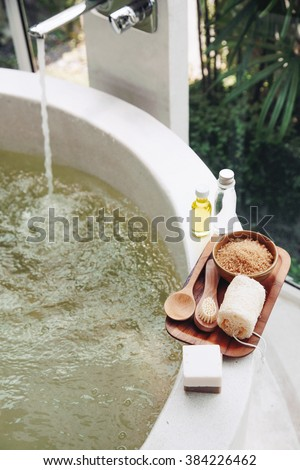 Spa decoration, natural organic products on a bathtube. Loofah, towel and frangipani flower.