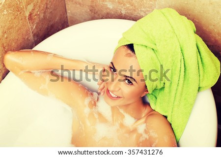 Spa happy woman relaxing in bath looking at camera - stock photo