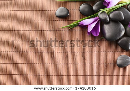 spa, heath and beauty concept - massage stones with flowers on mat - stock photo
