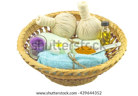 Spa herbal compressing ball , white frangipani flower (Apocynaceae, Pagoda tree,Temple tree),turmeric powder massage oil and blue fabric in bamboo basket  on white background.Saved with clipping path. - stock photo