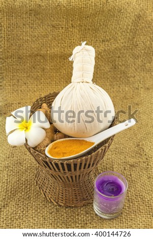 Spa herbal compressing ball , white frangipani flowers (Plumeria spp , Apocynaceae, Pagoda tree, Temple tree) , turmeric powder in white  spoon in bamboo basket  on brown fabric sack  background - stock photo