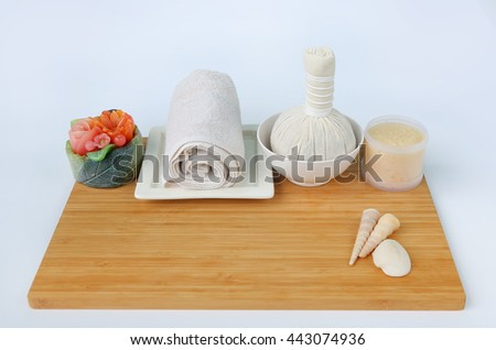 Spa herbal compressing ball with towels and Salt Scrub, Spa concept on bamboo board against white background