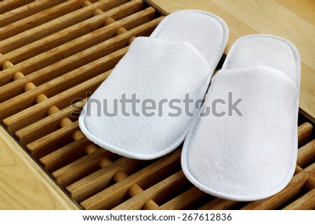 Spa, hotel - home slippers close on wooden planks floor - background with space for text - stock photo