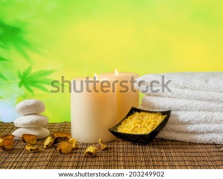Spa massage border background with towel stacked, candles and sea salt on bamboo table - stock photo