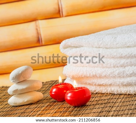 Spa massage border background with towel stacked stone and red candles on bamboo background