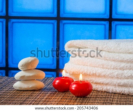 Spa massage border background with towel stacked stone and red candles on blue tiles background warm atmosphere - stock photo