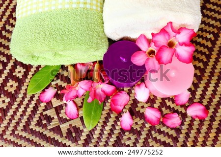Spa massage healthy setting with rolled towel,candlelight and beautiful flower on mat. - stock photo