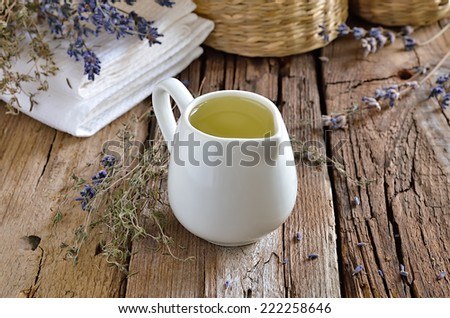 Spa massage herbal oil in a white jug - stock photo
