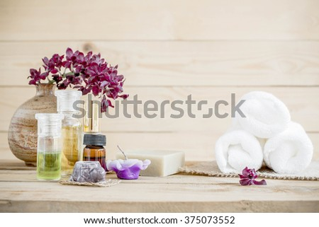 spa massage setting, orchid product, oil on wooden background. - stock photo